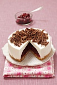 Cheesecake with cherry jam and chocolate curls, sliced