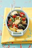 Potato casserole with olives, cherry tomatoes and rocket