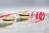 Two white chocolate macaroons with a spiral of red icing sugar