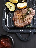 A grilled steak with rosemary, potatoes and barbeque sauce