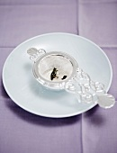 Tea strainer on a saucer
