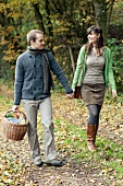 A couple with a picnic basket walking on the edge of a forest in autumn