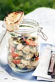 Pasta salad with shell pasta, tomatoes and olives for a picnic