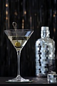 A Martini with an olive in a glass