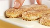 Preparing tiramisu: adding another layer of espresso biscuits