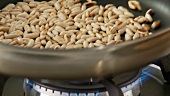 Pine nuts being roasted in a pan