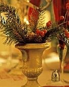Tannenzweige & Beeren in goldener Vase am Weihnachtstisch