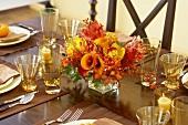 Blumendeko am herbstlich gedeckten Tisch
