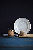 A stack of sugar biscuits and a ribbon, kitchen twine and a plate