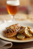 Grilled honey-glazed chicken with grilled potatoes and a glass of beer