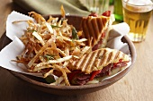 Pastrami and red pepper panini with shoe string fries and a glass of beer