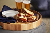 Bacon and tomato paninis on a tray with plates and two glasses of beer