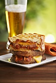 Corned beef and bacon panini with a glass of beer
