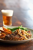 Peppered steak with onions, carrots, green beans and a glass of beer