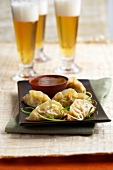 Won tons with a dip and glasses of beer (Asia)