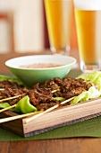 Vietnamese beef kebabs with a dip and glasses of beer