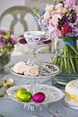 A cake stand with a tea cup, roses and chocolate eggs with a bunch of flowers in the background