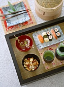 Japanese food, sushi and other Japanese nibbles, bowls, beakers on wooden tray, square dish, chop sticks, ceramics, crockery