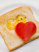 Fried eggs in toast, red pepper heart
