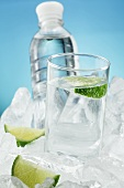 A glass of water and a bottle with limes on ice