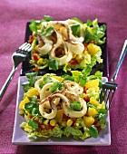 Zwei Salatteller mit Tintenfisch, Koriander, Mais und Ananas