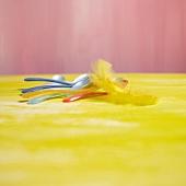 Bunte Eierlöffel und gelbe Federn
