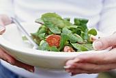 Junge Frau hält Salatteller