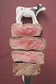 Steak slices & toy calf on carving fork (degrees of cooking)