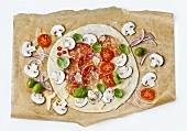 A raw pizza with salami and mushrooms on baking paper