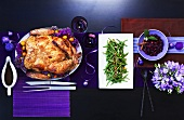 Chinese roasted turkey with green beans on a table with purple decorations