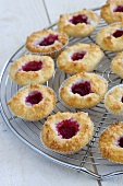 Coconut macaroons with raspberry jam on a wire rack