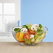 Salad ingredients in glass bowl in front of window