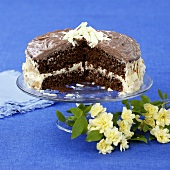 Chocolate almond cake on cake stand, a piece cut
