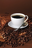 A cup of black coffee and coffee beans