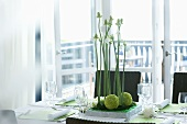 Laid dining table with flower arrangement, light balcony behind