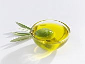A green olive in a small glass dish of olive oil