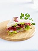 A ham, lettuce and radish sandwich