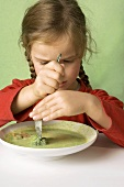 Girl cutting a broccoli floret in vegetable soup