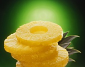 Five slices of pineapple in a pile with pineapple leaves