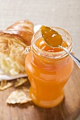 Apricot jam in jar with spoon, croissant