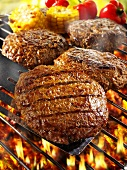 Burgers on barbecue rack and on spatula