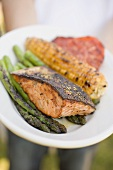 Person holding plate of grilled salmon, corn on the cob, vegetables