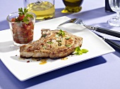 A pork chop with a glass of tomato salsa