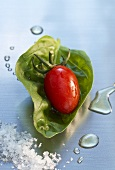 Grape tomato on a basil leaf with sea salt