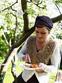 Woman eating salmon at smorgasbord in garden (Sweden)
