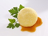 Potato dumpling with gravy and parsley