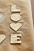 Cut-out 'LOVE' biscuits on baking parchment