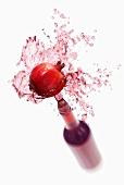 Pomegranate juice splashing out of bottle