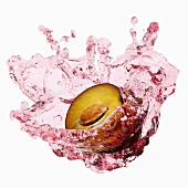 Half a plum with splashing plum juice