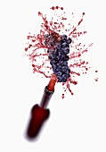 Red wine splashing out of bottle